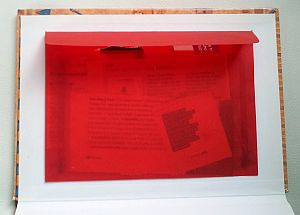 Une jolie enveloppe rouge transparente collée dans un cahier rigide